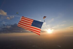 Skydiver performing with a large American flag